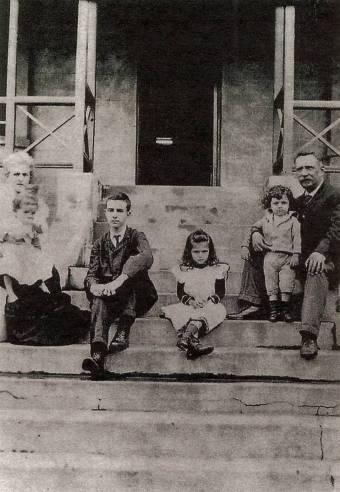 Pessoa na escadaria de sua casa em Durban com sua mãe, seu padrasto e três de seus cinco irmãos